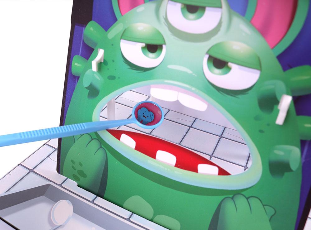 Осмотр зубов монстрика стоматологическим зеркальцем в  настольной игре Зубной для монстров