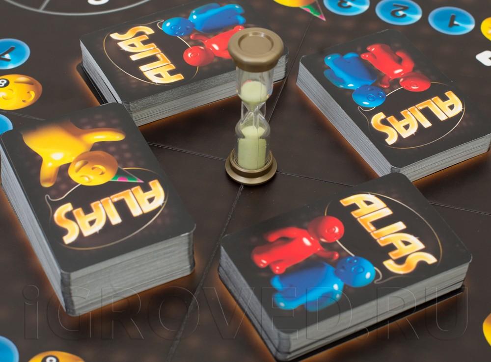 Карты и песочные часы на игровом поле Алиас для вечеринок